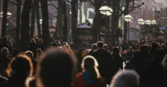 Back-lit crowd of people walking on street - stock footage