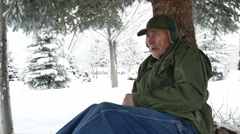 Aging homeless Vietnam era veteran seeks shelter from snow under a pine tree Stock Footage