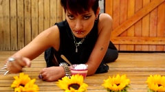 Rock inspired girl lying on wooden surface with cup of ice cream and sunflowers Stock Footage