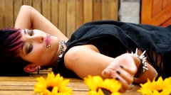 Rock inspired girl lying on wooden surface smelling sunflower then throws it Stock Footage