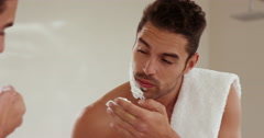 Handsome man putting shaving foam on face Stock Footage
