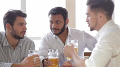 Happy friends catching up over pints in a bar - stock footage