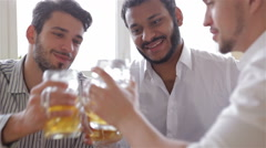 Happy friends clinking with beer mugs in pub - stock footage