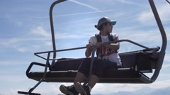 Stock Video Footage of Girl in chairlift high in the sky