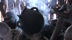 Hamer people tribe in Omo Valley boiling coffee over open fire in hut Stock Footage