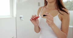 Beautiful woman applying lip gloss Stock Footage