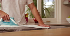 Midsection of a man ironing a shirt Stock Footage