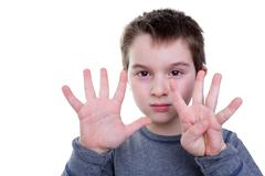 Child counting with eight fingers Stock Photos