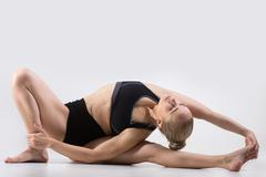 Variation of Head-to-Knee forward bend pose - stock photo
