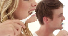 Couple wash their teeth with electronic toothbrush Stock Footage