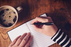 Woman drinking coffee and writing a diary note Stock Photos