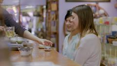 Two young caucasian girls being served tea by an Asian woman at a tea shop Stock Footage