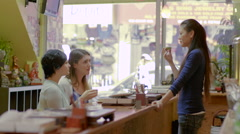 Asian woman converses and drinks tea with her customers at a teahouse, slow-mo Stock Footage