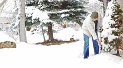 Aging man in coveralls shoveling snow Stock Footage