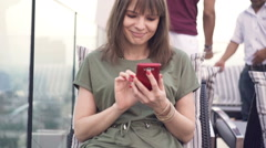 Young, pretty woman with smartphone sitting ar rooftop bar in the city Stock Footage
