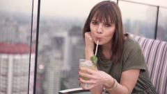Portrait of happy woman drinking cocktail at rooftop bar in the city Stock Footage