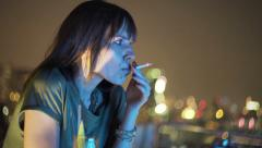 Pensive woman smoking cigarette at rooftop bar during night Stock Footage
