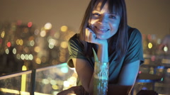 Portrait of happy woman sitting at rooftop bar during night Stock Footage