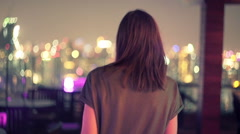 Young woman walking on terrace and admire city view during night Stock Footage