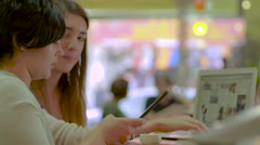 Two girls at a tea house using technology Stock Footage