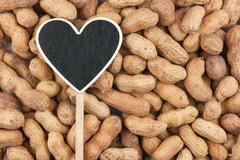 Pointer in the form of heart lies on peanut - stock photo
