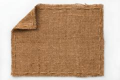 Frame of burlap with curled edges, lies on a white background Stock Photos