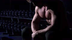 Muscular man in gym shows his muscles on his chest and torso Stock Footage