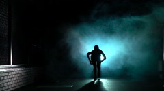 Sporty woman starts running in silhouette and smoke, front view, slow motion Stock Footage