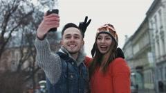 Sweet young couple making selfie on smartphone. Male and female in their 20s - stock footage