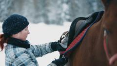 Stock Video Footage of Woman put on a saddle on a back of a horse