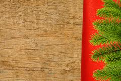 Red cloth with fir tree branch over wooden texture close-up - stock photo