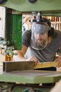Craftsman with safety mask visor handles band saw in workshop Stock Photos