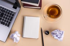 Office table desk with supplies, white blank note pad, cup, pen, pc, crumpled - stock photo