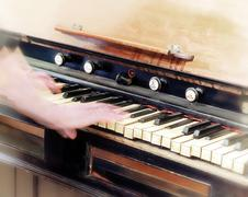 Female hands hit the keys of the old piano - stock photo