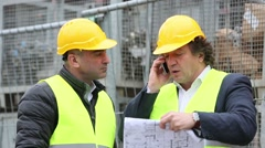 Engineer at phone and construction manager discussing blueprints and drawings - stock footage