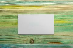 White blank business visit card, gift, ticket, pass, present close up on blurred - stock photo