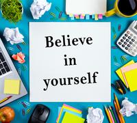 Believe in yourself. Office table desk with supplies, white blank note pad, cup - stock photo