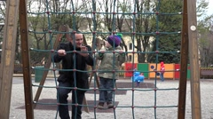 Father teaching little son to clim on rope ladder at playground, cheerful family Stock Footage