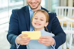 Young adoring dad taking picture of cute daughter - stock photo