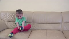 Sweet little boy dressing himself, clumsy arranging his socks, childhood fashion - stock footage