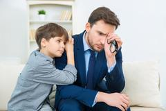 Father is feeling worry while son trying to comfort him Stock Photos