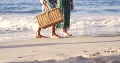 Mid section of mature couple walking on the sand Stock Footage