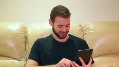 Young man smiling and touching screen on his iPad mini at home - stock footage