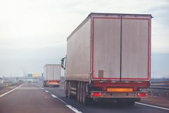 Commercial trailer truck in motion on freeway on cloudy afternoon Stock Photos