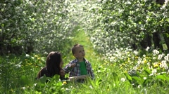 Stock Video Footage of Young mother and little son blowing bubbles, having fun in blossom orchard