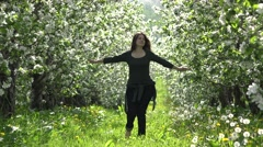 Attractive young woman rotating in blossom orchard, enjoying nature Stock Footage