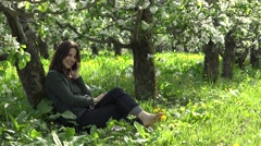 Beautiful young woman speak on the phone, feeling free barefoot, bloom orchard Stock Footage