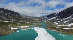 Flight above frozen lake in mountain pass in Norway Stock Footage