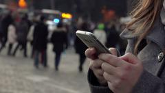 closeup woman's hands texting on the mobile phone in the city at the dusk - stock footage