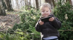 Stock Video Footage of Little kid girl watch smart phone cartoons outdoor in forest park nature